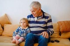 Leuk tonen weinig peutermeisje en grootvader die samen op TV letten Babykleindochter en gelukkige teruggetrokken hogere mens stock afbeeldingen