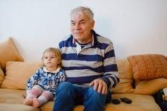 Leuk tonen weinig peutermeisje en grootvader die samen op TV letten Babykleindochter en gelukkige teruggetrokken hogere mens royalty-vrije stock fotografie