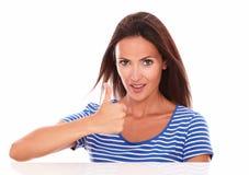 Leuk vriendschappelijk meisje met omhoog duimen Stock Fotografie