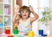 Leuk vrolijk jong geitjemeisje die haar die vingers tonen in heldere kleuren worden geschilderd royalty-vrije stock afbeeldingen