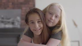Leuk weinig albinomeisje die haar donkerbruin meisje, vrienden koesteren die camera het glimlachen bekijken Concept vriendschap stock video