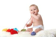 Leuk weinig baby die met ballen van wol speelt Stock Afbeeldingen