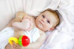 Leuk weinig baby die met stuk speelgoed rammelaar en eigen voeten na het nemen van bad spelen Aanbiddelijk mooi die meisje in wit Royalty-vrije Stock Foto's