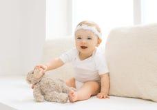 Leuk weinig baby die met stuk speelgoed thuis in witte ruimte spelen Royalty-vrije Stock Foto's