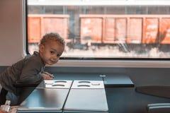 Leuk weinig babyjongen die door spoorweg reizen stock foto's