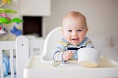 Leuk weinig babyjongen, die fijngestampte groenten voor lunch, mammafe eten stock afbeeldingen