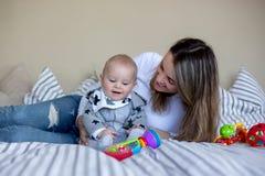 Leuk weinig babyjongen, die met zijn mamma thuis in bed met l spelen Royalty-vrije Stock Foto
