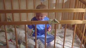 Leuk weinig babyjongen onder een dollarregen in bed Concept erfenis stock footage