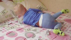 Leuk weinig babyjongen onder een dollarregen in bed Concept erfenis stock videobeelden