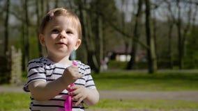 Leuk weinig babymeisje die met haar speelgoed spelen die in een zandbak bij een speelplaats zitten stock videobeelden