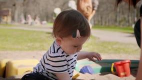 Leuk weinig babymeisje die met haar speelgoed spelen die in een zandbak bij een speelplaats zitten stock footage