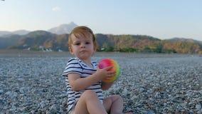 Leuk weinig babymeisje die met kleurrijke bal in handen op een strand zitten stock footage