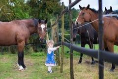 Leuk weinig babymeisje die met paarden op een landbouwbedrijf spelen Royalty-vrije Stock Fotografie