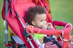 Leuk weinig babymeisje in een wandelwagen stock foto