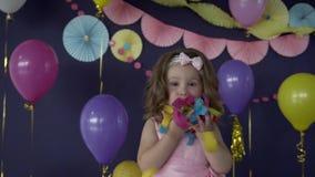 Leuk weinig blazende confetti van het babymeisje op haar verjaardagspartij stock footage