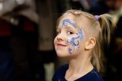 Leuk weinig blond meisje met gezicht het schilderen Blauw abstract sneeuwvlokpatroon door waterverf op jonge geitjesgezicht Aanbi stock foto