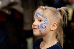 Leuk weinig blond meisje met gezicht het schilderen Blauw abstract sneeuwvlokpatroon door waterverf op jonge geitjesgezicht Aanbi stock foto's