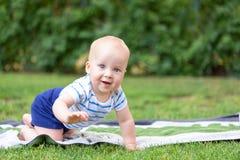Leuk weinig blonde babyjongen die op vers groen gras kruipen Jong geitje die pret hebben die eerste stappen op gemaaid natuurlijk stock foto