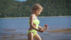 Leuk weinig blondemeisje die door een meer met de groene bergen op de achtergrond lopen stock video
