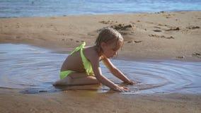 Leuk weinig blondemeisje die met het zand bij een meer spelen stock videobeelden
