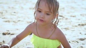 Leuk weinig blondemeisje die met het zand bij een meer spelen stock footage