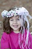 Leuk weinig die gir met bloemen in hairl glimlacht Royalty-vrije Stock Afbeeldingen