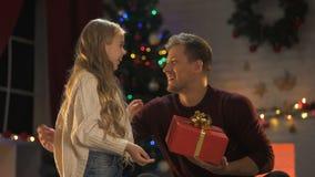 Leuk weinig dochter die Kerstmis huidig voor gelukkige papa, lichten het fonkelen geven stock footage