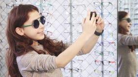 Leuk weinig gelukkig meisje die selfies bij de eyewear opslag nemen stock videobeelden
