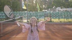 Leuk weinig glimlachend gelukkig meisje met een tennisracket in haar handen die zich op de tennisbaan bevinden die de camera onde stock videobeelden