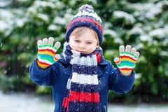 Leuk weinig grappige jong geitjejongen in de kleurrijke kleren die van de de wintermanier pret hebben en met sneeuw, in openlucht stock fotografie