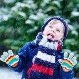 Leuk weinig grappige jongen in kleurrijke de winterkleren die pret hebben met royalty-vrije stock foto