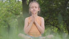 Leuk weinig het meisjeszitting van Ute op gras het mediteren De yoga van kindpraktijken Zomervrije tijd stock footage