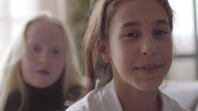 Leuk weinig het vlechten lang haar van het albinomeisje van haar donkerbruin meisje Concept vriendschap Onbezorgde kinderjaren stock video