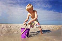 Leuk Weinig Jong geitje het Spelen met Zand in een Emmer bij het Strand door de Oceaan stock afbeeldingen