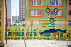 Leuk weinig jong geitjejongen die beklimmend atletische ringen op een speelplaats genieten van Peuterkind die leren te beklimmen, stock fotografie