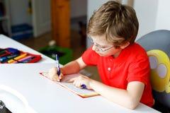 Leuk weinig jong geitjejongen met glazen die thuis thuiswerk maken, schrijvend brieven met kleurrijke pennen stock afbeelding