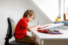 Leuk weinig jong geitjejongen met glazen die thuis thuiswerk maken, schrijvend brieven met kleurrijke pennen royalty-vrije stock afbeelding