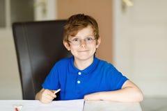 Leuk weinig jong geitjejongen met glazen die thuis thuiswerk maken, schrijvend brieven met kleurrijke pennen stock afbeeldingen