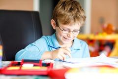Leuk weinig jong geitjejongen met glazen die thuiswerk maken, thuis schrijvend brieven en wiskunde met kleurrijke pennen doen wei stock afbeelding