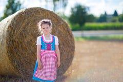Leuk weinig jong geitjemeisje in traditioneel Beiers kostuum op tarwegebied stock afbeeldingen