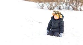 Leuk weinig jongen die in de wintersneeuw knielen Stock Foto's
