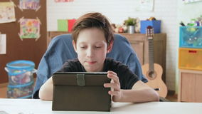 Leuk weinig jongen die digitale tablet gebruiken die Internet doorbladeren stock videobeelden