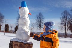 Leuk weinig jongen die een sneeuwman maken, die in de sneeuw spelen royalty-vrije stock fotografie