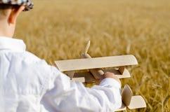 Leuk weinig jongen die een stuk speelgoed vliegtuig in een wheatfield vliegen Stock Foto