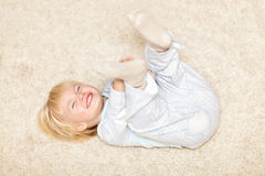 Leuk weinig jongen die en op de vloer glimlacht speelt stock fotografie