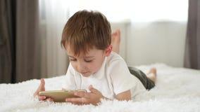 Leuk weinig jongen die gebruikend smartphone spelen Het kind bekijkt het smartphonescherm en lacht Toepassingen voor stock footage