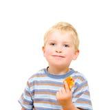 Leuk weinig jongen die heerlijk geïsoleerd koekje eten stock foto