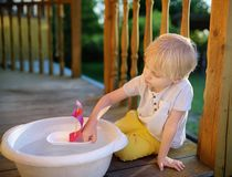 Leuk weinig jongen die met een eigengemaakte boot in een bassin water op de portiek van een huis spelen Jonge geitjesspel stock foto