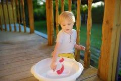 Leuk weinig jongen die met eigengemaakt schip in bassin water op de portiek van huis spelen Jonge geitjesspel royalty-vrije stock foto