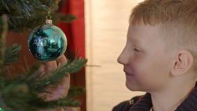 Leuk weinig jongen die met Kerstmisbal spelen stock video